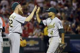 Oakland Athletics relief pitcher Sean Doolittle, left, celebrates with teammate left fielder Coco Crisp after defeating the Los Angeles Angels in a baseball game Saturday, June 25, 2016, in Anaheim, Calif. The Athletics won, 7-3. (AP Photo/Gregory Bull)