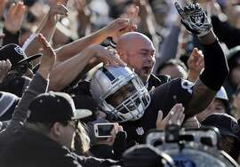 Clive Walford (88) leaps into the black hole after scoring a touchdown in the first half as the Raiders played the Minnesota Vikings at O.co Coliseum in Oakland, Calif., on Sunday, November 15, 2015.