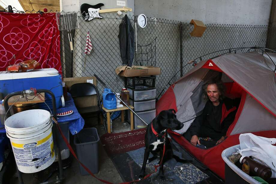 Jim James, 55, and his dog Sophia emerge from their tent in the morning underneath an overpass on Brush street Aug. 10, 2016 in Oakland, Calif. James has been homeless for about seven years and he attributes it to his drug addiction problems combined with the loss of his father. James says he has seen the homeless population grow recently in Oakland and has noticed people coming over from San Francisco. Photo: Leah Millis, The Chronicle