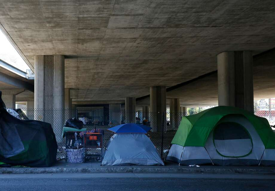 Tents cluster underneath an overpass on Brush Street in Oakland. Photo: Leah Millis, The Chronicle