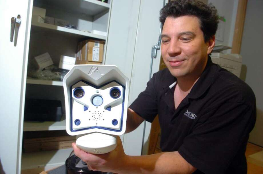 "Scott Sebastian, director of sales for Omni Data, holds out a camera resembling a ""Storm Trooper"" Thursday Apr. 29, 2010 at his company's Woodbridge office.  Omni Data produces security cameras and software that is being installed in public places, including Fairfield University, Seymour parks and the streets of Milford. Photo: Autumn Driscoll / Connecticut Post"
