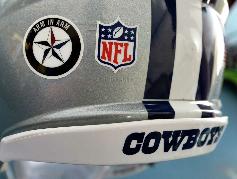 """The NFL has ruled that the Dallas Cowboys can only wear this """"Arm in Arm"""" decal supporting the Dallas Police department during training camp practices, but not in preseason or regular-season games. Photo: Max Faulkner, TNS / Fort Worth Star-Telegram"""