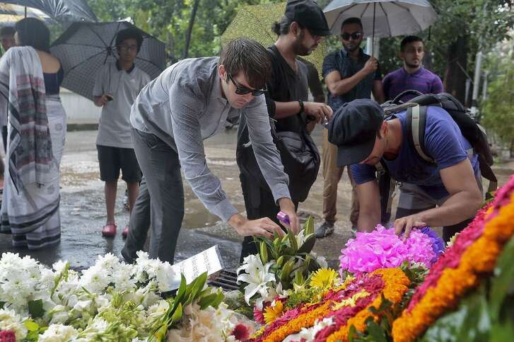 People offer flowers to pay their respects to the victims of the attack on Holey Artisan Bakery, in Dhaka, Bangladesh, Tuesday, July 5, 2016. The attack, the worst convulsion of violence yet in the recent series of deadly attacks to hit Bangladesh, has stunned the traditionally moderate Muslim nation and raised global concerns about whether it can cope with increasingly strident Islamist militants. (AP Photo)