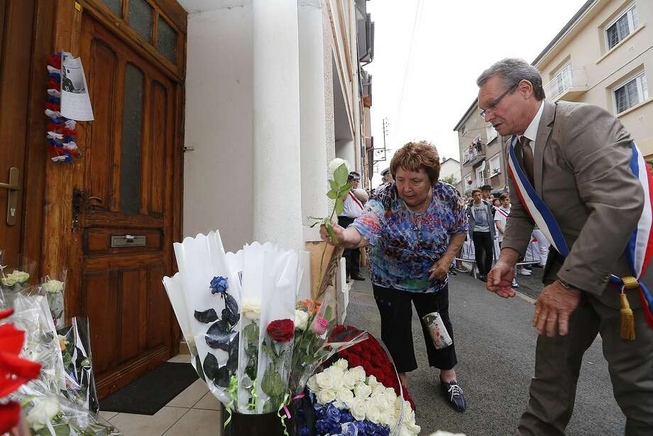 Jacqueline Locatelli, sister of a victim (L), and Gerard Didelot, Herserange Mayor, lay flowers in front of the home of Christiane, Francois, Veronique, Michael, Gisele and Germain, six members of a family who died during July 14 Nice terror attack, on July 20, 2016 in Herserange. Photo: FRED MARVAUX, AFP/Getty Images