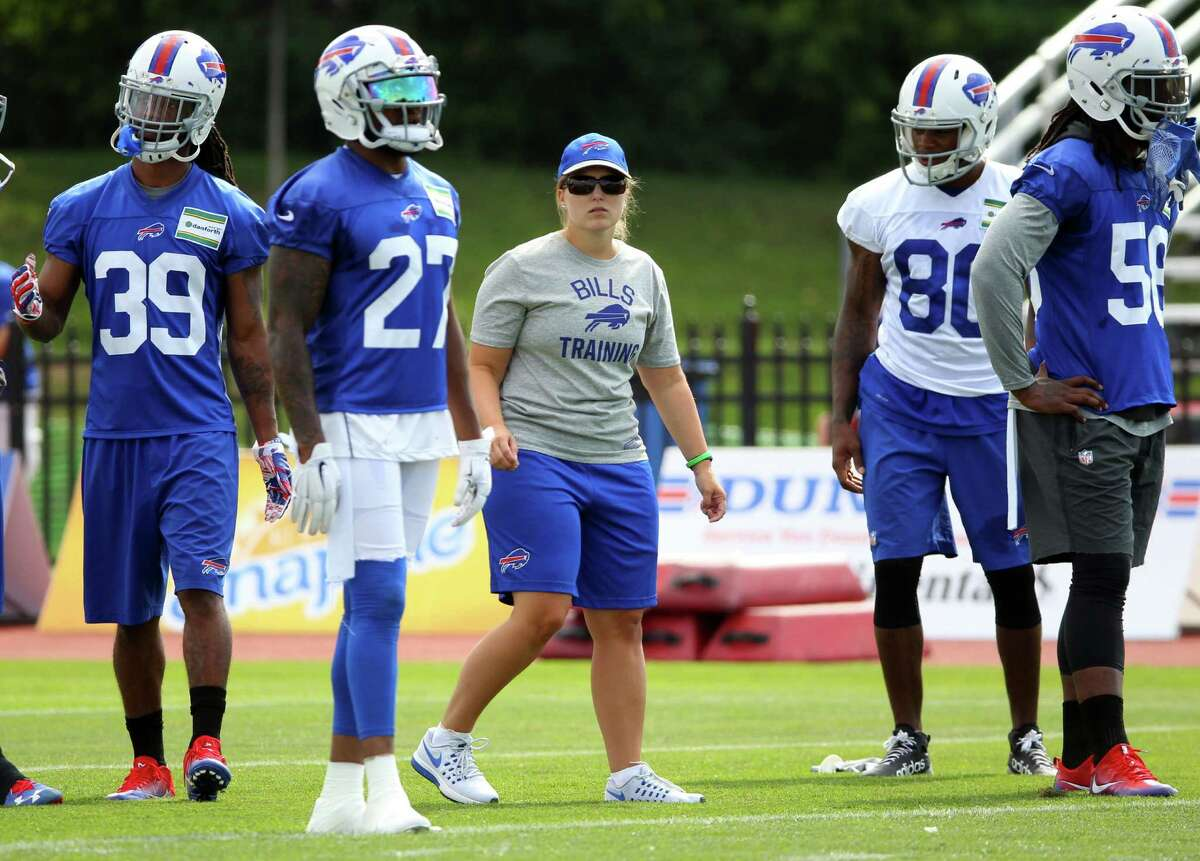 FILE - In this July 31, 2016, file photo, Buffalo Bills quality control-special teams coach Kathryn Smith works with players during NFL football training camp in Pittsford, N.Y. Shy, reserved and unaccustomed to the spotlight, Smith has difficulty putting into perspective what it's like to be the NFL's first female assistant coach and the nationwide publicity she has drawn, including catching the attention of Chelsea Clinton on Twitter. And yet, there is one thing the Bills coach is sure of: It won't be long, Smith says, before other women join her on the sidelines. (AP Photo/Bill Wippert, File) ORG XMIT: NY156