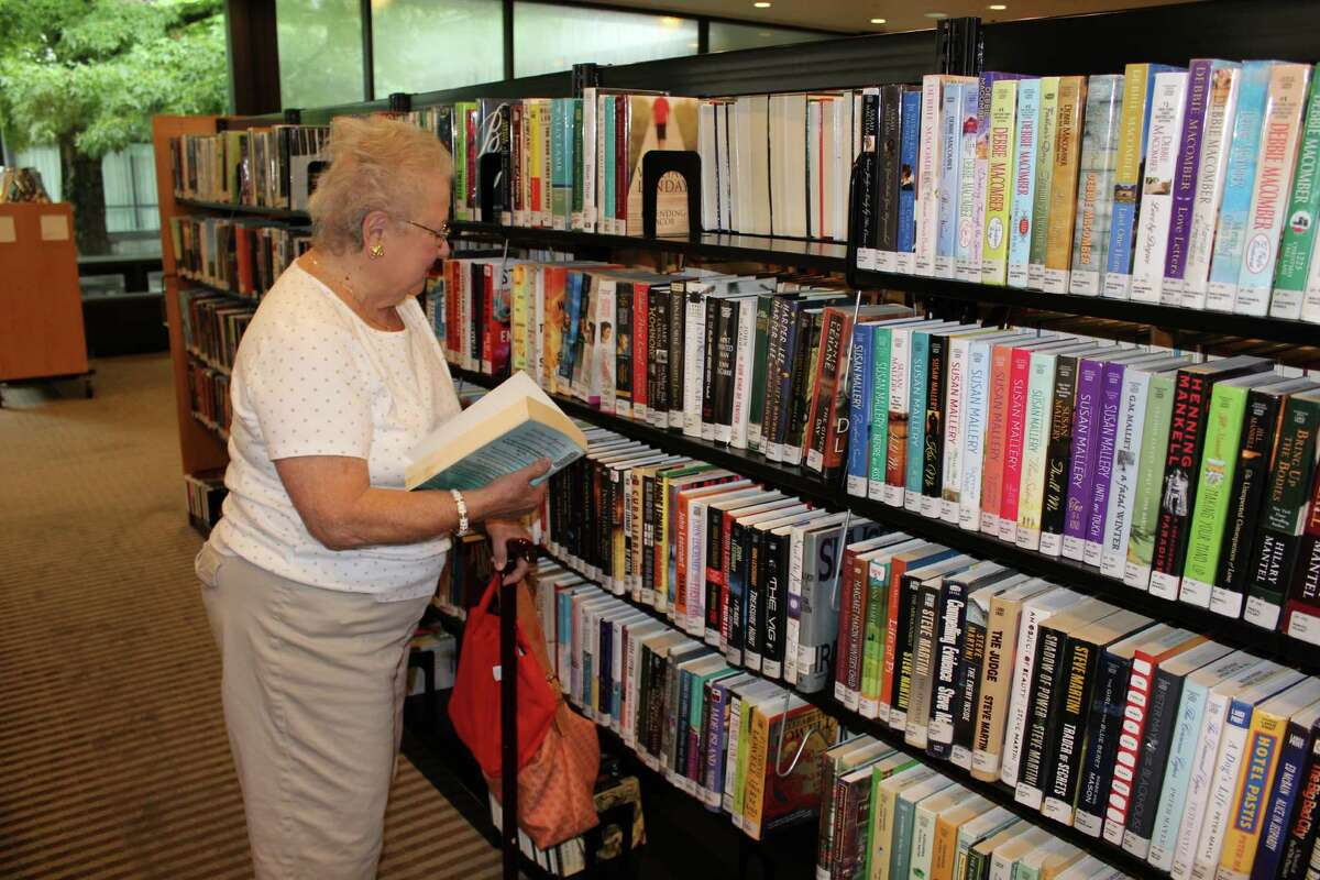 A Wilton resident walks the aisles at the Wilton Library searching for new book to read. Book rentals are only one of the services provided to the public by the library.