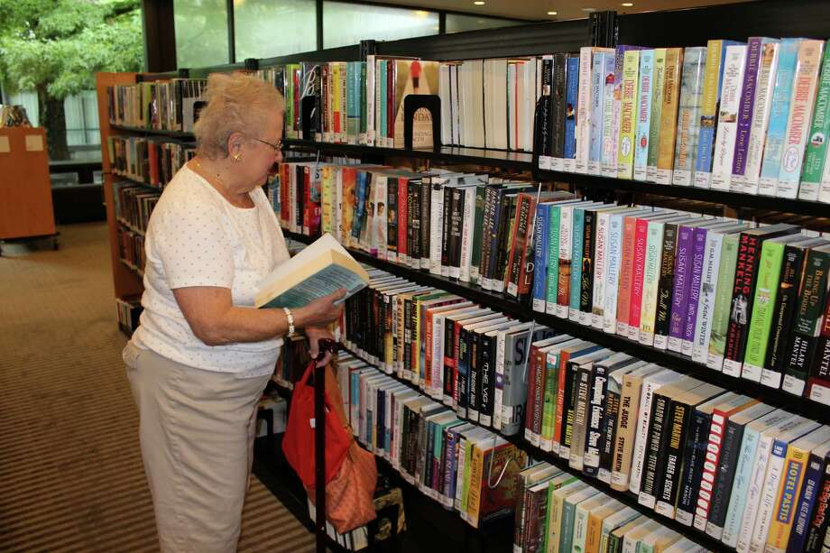 A Wilton resident walks the aisles at the Wilton Library searching for new book to read. Book rentals are only one of the services provided to the public by the library. Photo: Pat Tomlinson / Hearst Connecticut Media