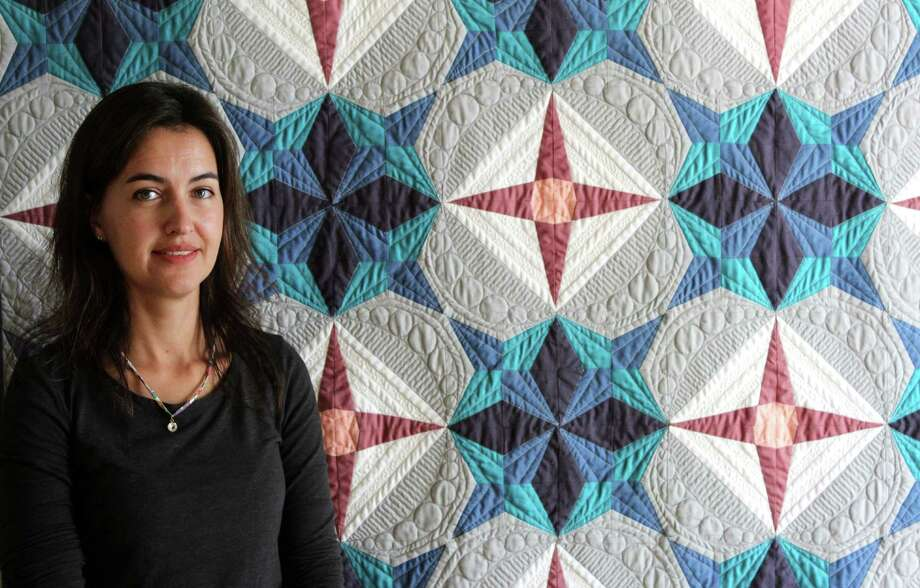 """Carolina Asmussen, of Wilton, stands in front of her first quilt, """"Origami Stars."""" Photo: Stephanie Kim / Hearst Connecticut Media"""