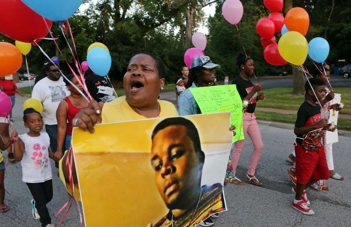 Sharon Cowan chants as she marches on the way to a candle light vigil on the spot where Mike Brown was killed on Tuesday, Aug. 9, 2016, in Ferguson, Mo. The demonstration marked two years since the unarmed black 18-year-old's fatal shooting by a white police officer. (J.B. Forbes/St. Louis Post-Dispatch via AP) ORG XMIT: MOSPT321