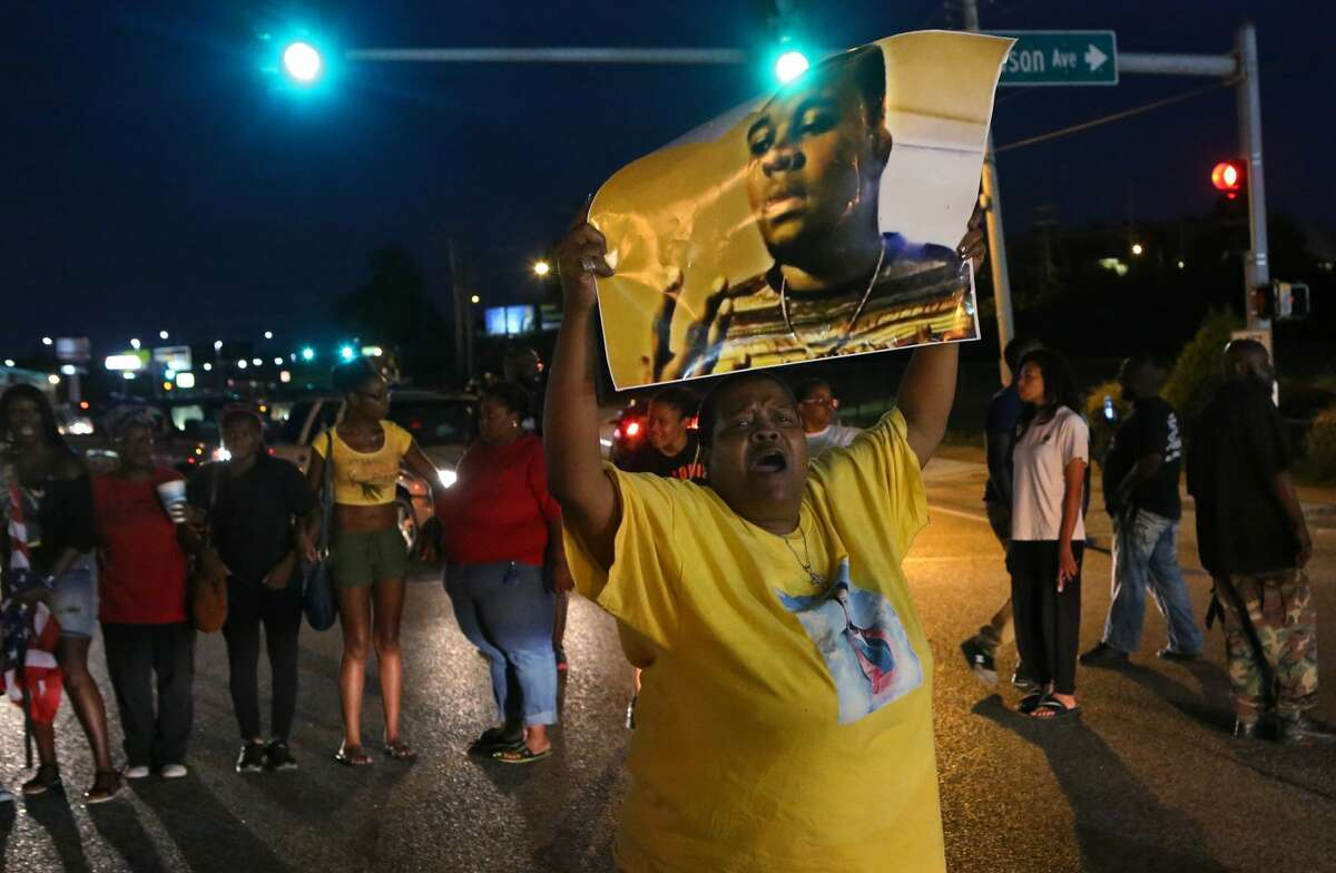 Sharon Cowan chants as she marches Tuesday, Aug. 9, 2016, in Ferguson, Mo., on the second anniversary of the death of Michael Brown, an unarmed black 18-year-old who was shoot by a white police officer. (J.B. Forbes/St. Louis Post-Dispatch via AP) ORG XMIT: MOSPT322