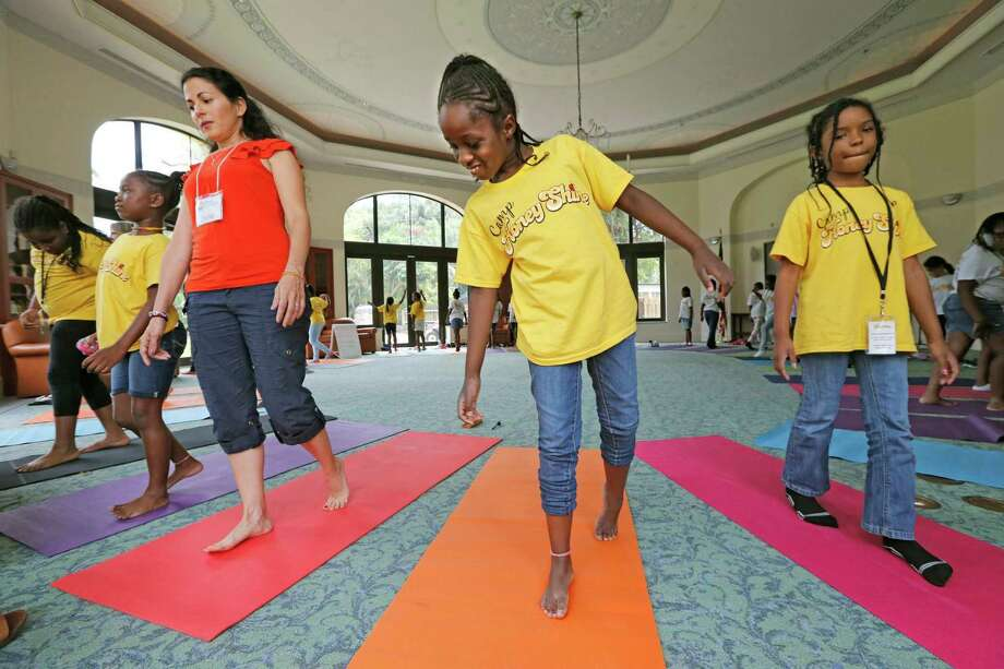 """Program coordinator Dorlisa Banbanaste works with students Cambriyah Noldon and Dakota Davis, left to right, during a """"mindfulness"""" workshop on methods to cope with stress in a class room. Photo: Al Diaz /TNS / Miami Herald"""