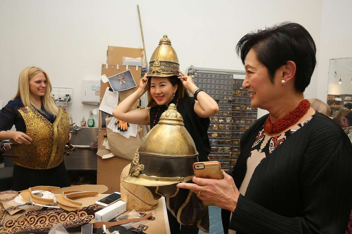 """Senior production supervisor Kristi Johnson (left) show Gorretti Lui (middle) and Doreen Woo Ho (right) , co-chairs of the world premiere of Chinese-themed opera, """"Dream of the Red Chamber,"""" soldiers gear and helmets in the SF opera costume studio on Thursday, July 21, 2016, in San Francisco, Calif."""