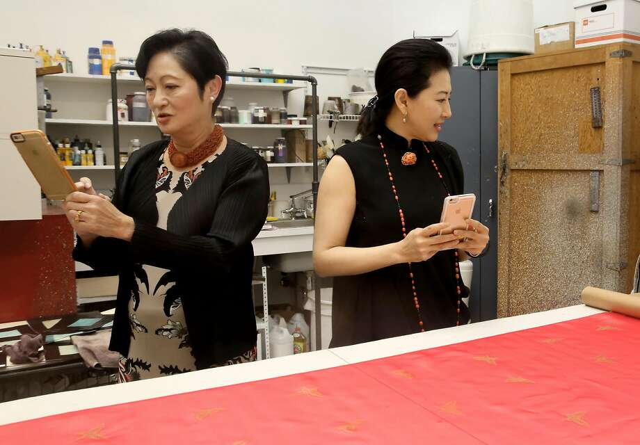 "Doreen Woo Ho (left) and Gorretti Lui, co-chairs of the world premiere of the Chinese-themed opera ""Dream of the Red Chamber,"" look at hand-painted materials in the S.F. Opera's costume studio. Photo: Liz Hafalia, The Chronicle"