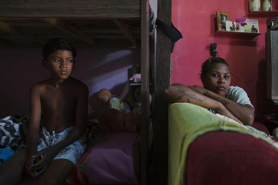Richard Conceicao Dias, 9, shares a one-room home with his mother (right) and three sisters. Photo: LALO DE ALMEIDA, NYT