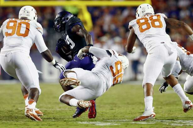 Jordan Moore (29) of the TCU Horned Frogs carries the ball against Chris Whaley (96), Malcom Brown (90) and Cedric Reed (88) of the Texas Longhorns in the first quarter at Amon G. Carter Stadium on Oct. 26, 2013 in Fort Worth.
