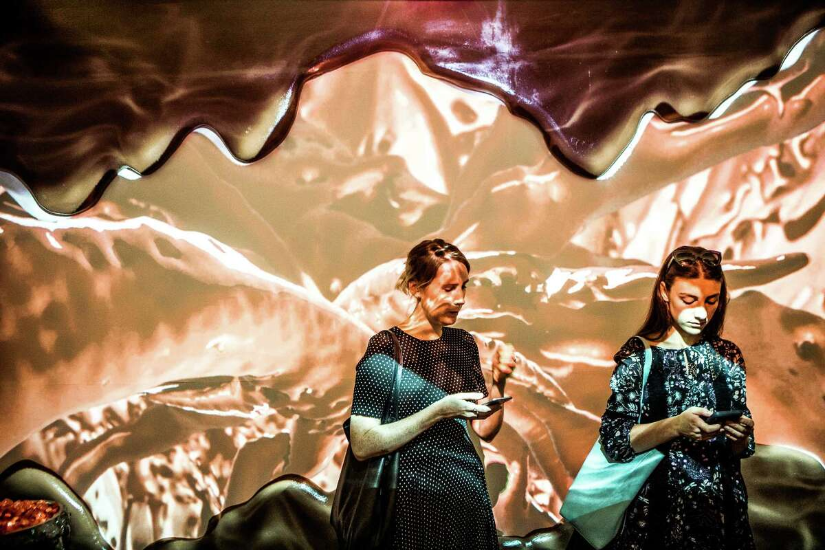 Attendees pass through the chocolate room, where projections of liquid chocolate swirl along the wall, during a press preview of the Museum of Ice Cream in New York, July 28, 2016. The sold-out spectacle uses art installations mixed with taste experiments to tap into childlike memories of summer days and ice cream cones. (George Etheredge/The New York Times) ORG XMIT: XNYT177