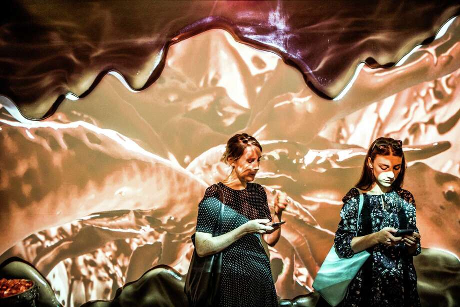 Attendees pass through the chocolate room, where projections of liquid chocolate swirl along the wall, during a press preview of the Museum of Ice Cream in New York, July 28, 2016. The sold-out spectacle uses art installations mixed with taste experiments to tap into childlike memories of summer days and ice cream cones. (George Etheredge/The New York Times) ORG XMIT: XNYT177 Photo: GEORGE ETHEREDGE / NYTNS