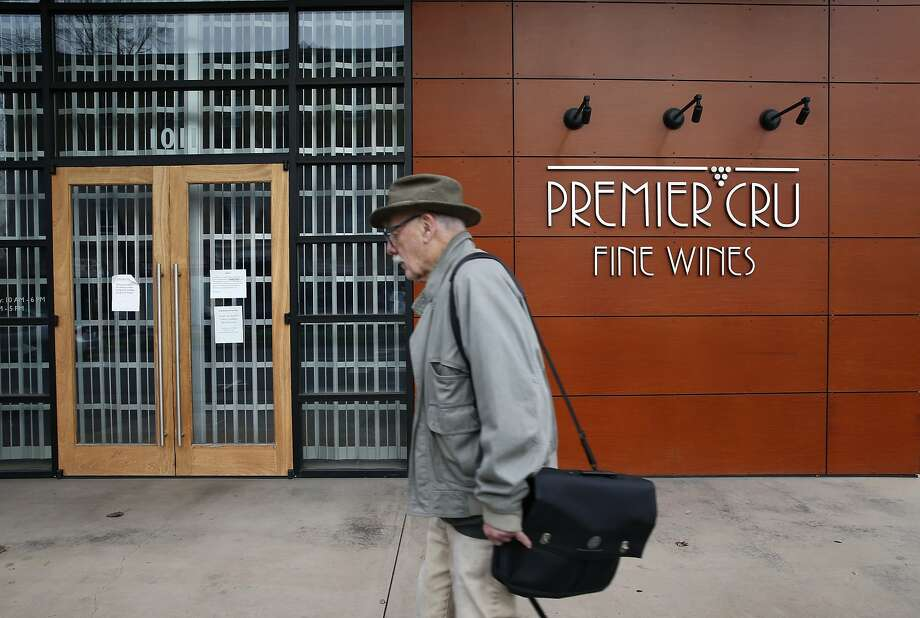 "A man walks past the shuttered Premier Cru wine store on University Avenue in Berkeley, Calif. on Thursday, Jan. 14, 2016. Store owner John Fox pleaded guilty Aug. 11, 2016, to defrauding customers out of at least $45 million, in what a judge described as a ""wine Ponzi scheme."" Photo: Paul Chinn, The Chronicle"