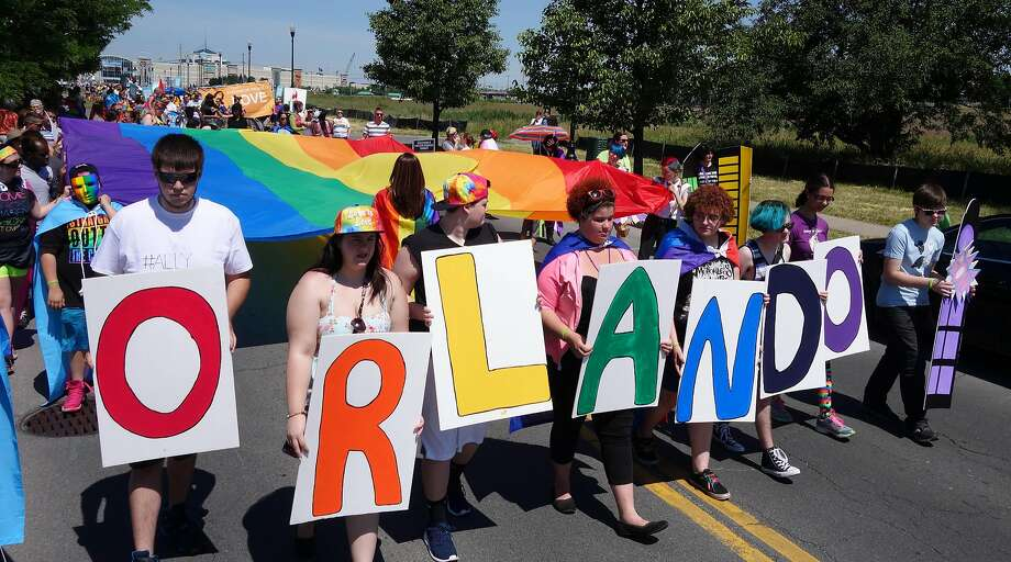 People in Syracuse, N.Y., commemorate the mass shooting at a gay nightclub in Orlando in June. Photo: Michael Greenlar, Associated Press