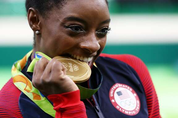 RIO DE JANEIRO, BRAZIL - AUGUST 11:  Gold medalist Simone Biles of the United States poses for photographs after the medal ceremony for the Women's Individual All Around on Day 6 of the 2016 Rio Olympics at Rio Olympic Arena on August 11, 2016 in Rio de Janeiro, Brazil.  (Photo by Elsa/Getty Images)