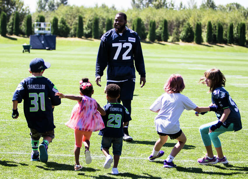 Michael Bennett holds a kids footrace on the field after finishing training camp at Virginia Mason Athletic Center in Renton on Thursday, Aug. 11, 2016. (Lacey Young, seattlepi.com)