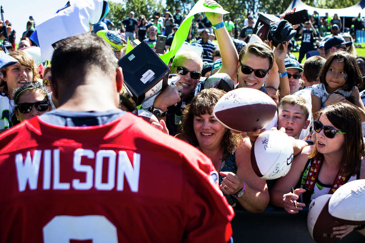 Fans hold memorabilia out in hopes of having Seahawks quarterback Russell Wilson sign it after training camp at Virginia Mason Athletic Center in Renton on Thursday, Aug. 11, 2016. (Lacey Young, seattlepi.com)