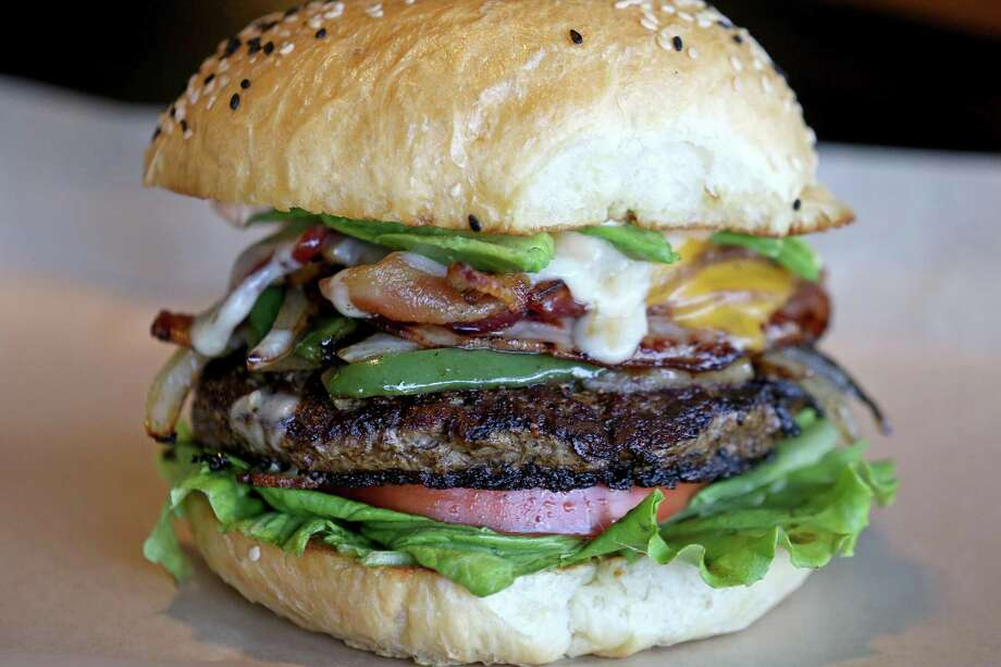 The Norteño Burger includes ham, bacon, cheddar and Oaxaca cheeses, grilled onions, avocado, lettuce, tomato and chipotle aioli. Photo: Edward A. Ornelas /San Antonio Express-News / © 2016 San Antonio Express-News