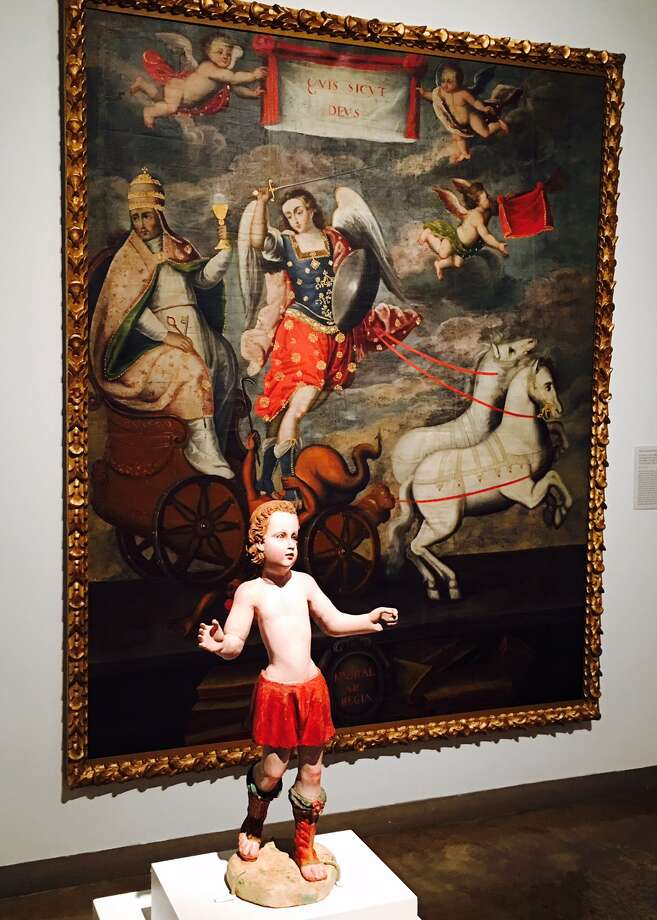 """""""Triumph of Saint Michael the Archangel,"""" Peruvian, late 17th- or early 18th century, hangs behind a wood statue of a child archangel, in """"Highest Heaven,"""" an exhibit on view at the San Antonio Museum of Art through Sept. 4. Photo: Elaine Ayala/San Antonio Express-News"""