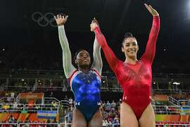 US gymnast Simone Biles (L) and  her compatiot Alexandra Raisman celebrate after the women's individual all-around final of the Artistic Gymnastics at the Olympic Arena during the Rio 2016 Olympic Games in Rio de Janeiro on August 11, 2016. US gymnast Simone Biles won the event ahead of her compatiot Alexandra Raisman and Russia's Aliya Mustafina. / AFP PHOTO / EMMANUEL DUNANDEMMANUEL DUNAND/AFP/Getty Images