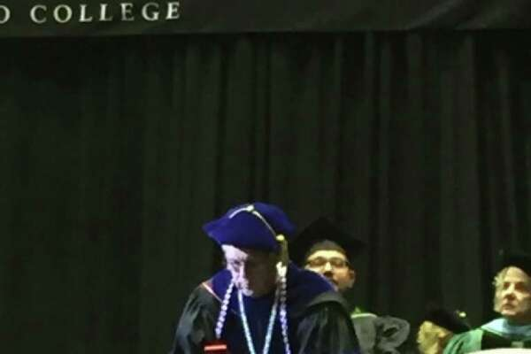 Alamo Colleges Chancellor Bruce Leslie focuses on his smartphone during a spring Alamo Colleges graduation ceremony. The episode has sparked continuing ramifications.