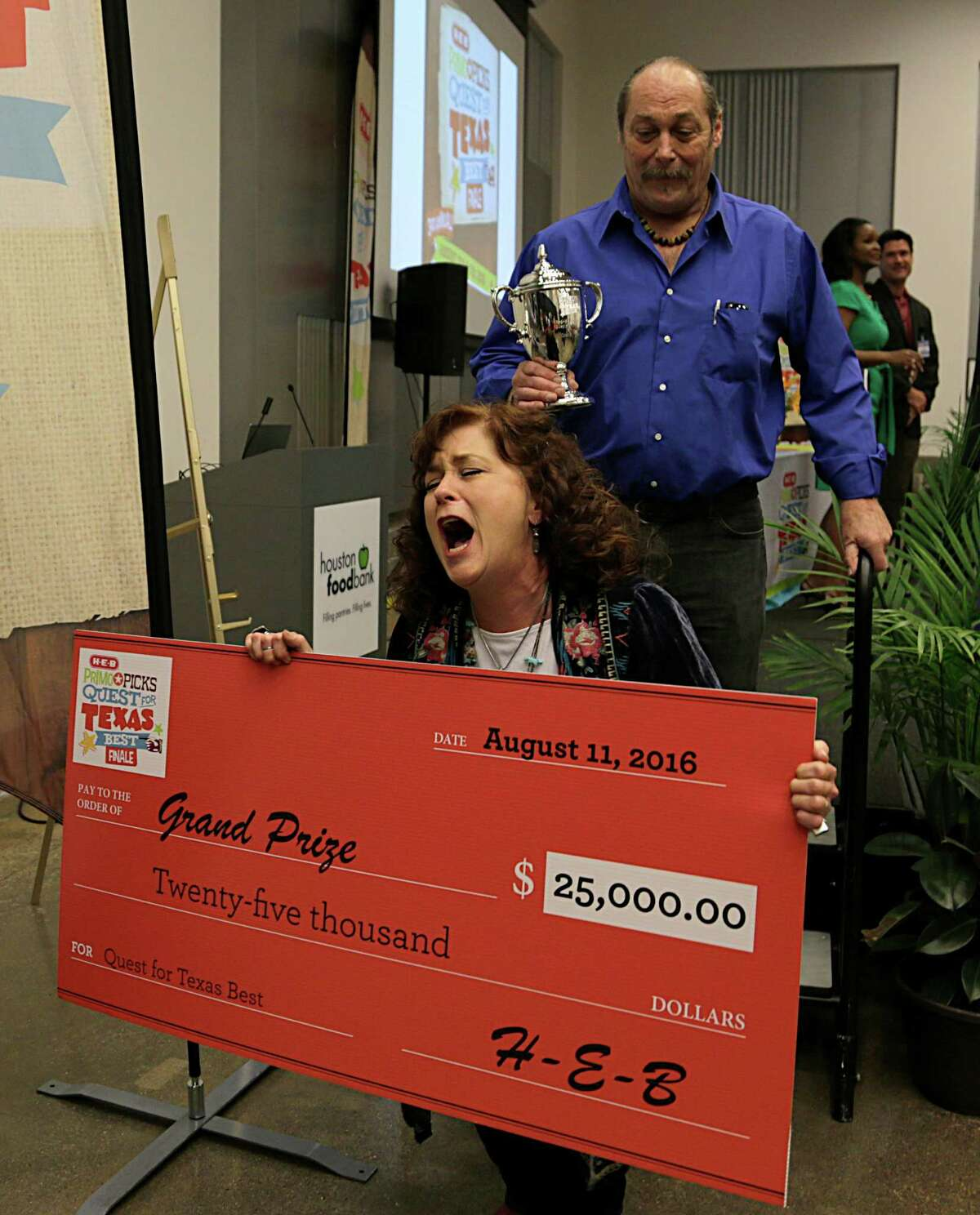 The Texas Pie Company's Chef Julie Albertson left, and her husband Spencer Thomas right, react after winning the Grand Prize with her Original Pie Dough Puck in the H-E-B Quest for Texas Best competition finals at the Houston Food Bank Aug. 11, 2016, in Houston. ( James Nielsen / Houston Chronicle )