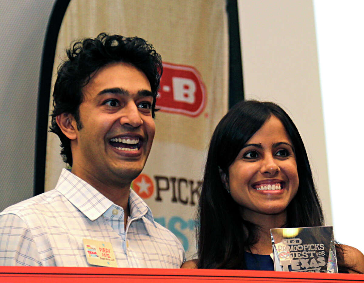 Bagel Dots' Purav Patel left, Aarti Garehgrat right, stand on the stage after winning one of two 1st place awards for their Bagel Dots in the H-E-B Quest for Texas Best competition at the Houston Food Bank Aug. 11, 2016, in Houston.