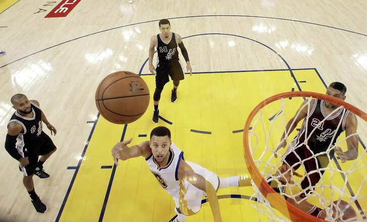 Stephen Curry (30) shoots under the basket in the first half as the Golden State Warriors played the San Antonio Spurs at Oracle Arena in Oakland Calif., on Thursday, April 7, 2016.
