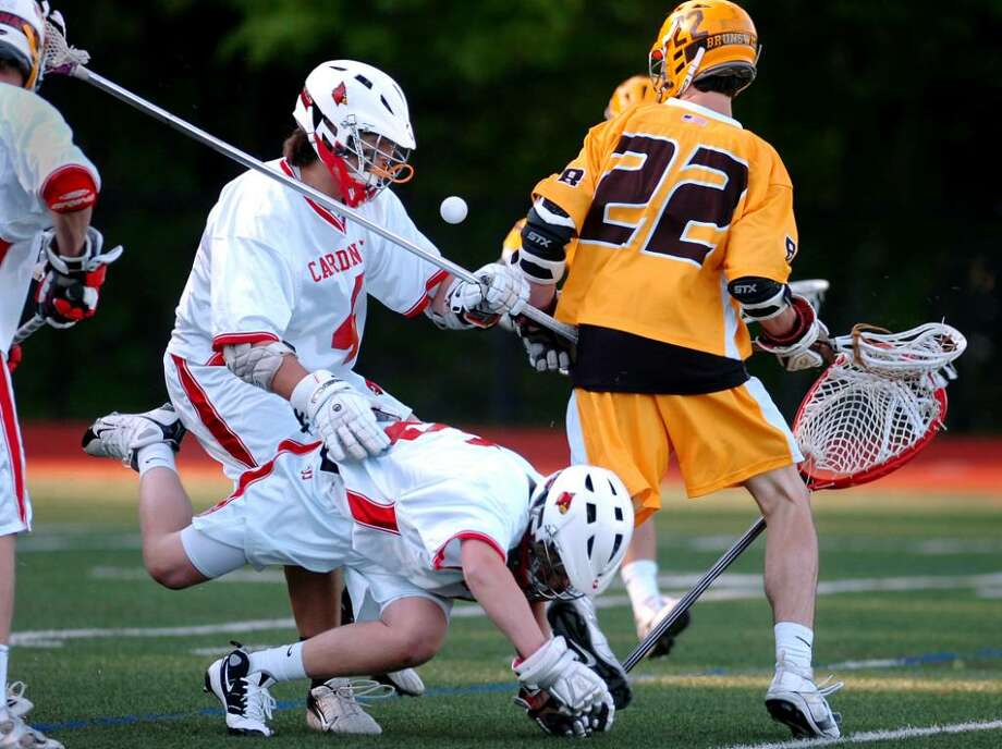 Greenwich High School goalie, Ryan Fisher, tumbles to the ground as teammate, Adam Sands, # 4, left, fights John Kelly, # 22, of Brunswick for the ball during late game action at GHS, Thursday, April, 29, 2010.  The Bruins defeated the Cardinals, 15-7. Photo: Bob Luckey / Greenwich Time