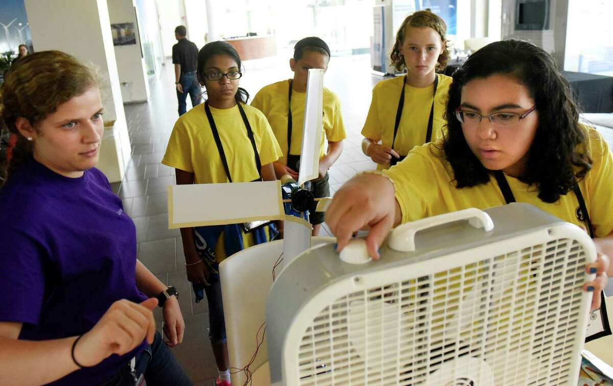 Liliana Soto, 12, right, turns on the fan to test the wind turbine she built with her Oneida Middle School classmates during the 5th annual GE Girls summer STEM experience on Thursday, Aug. 11, 2016, at General Electric in Schenectady, N.Y. Assisting the team is GE intern Maria Perez Luna, left. (Cindy Schultz / Times Union)