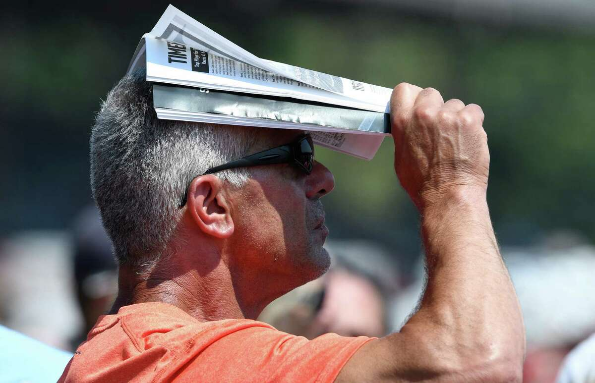 A racing patron uses his racing program to get a small amount of shade during first race at the Saratoga Race Course Thursday Aug. 11, 2016 in Saratoga Springs, N.Y. (Skip Dickstein/Times Union)