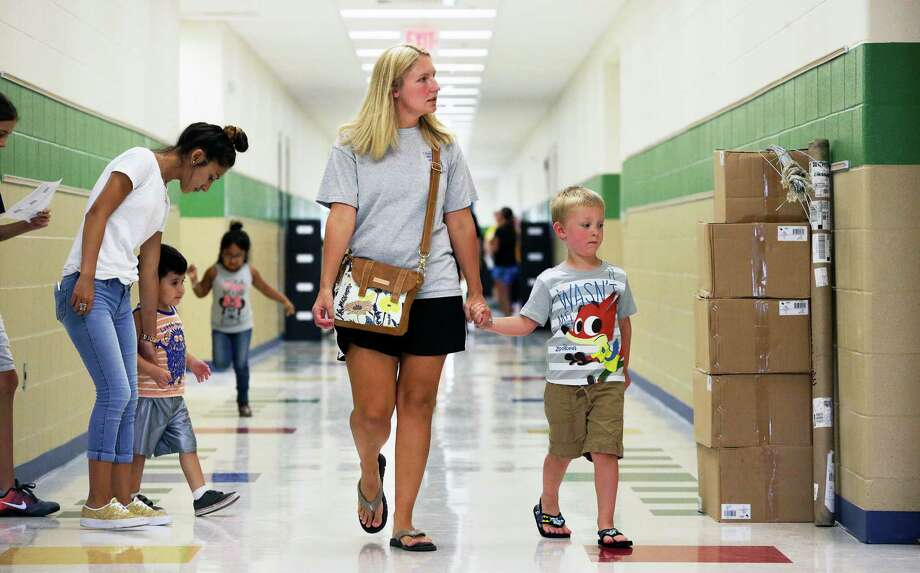 Lisa Richardson checks out a room with son Noah as moms lead their kids through the hallways around packing boxes and file cabinets during a special sneak peek at the brand new Randall H. Fields Elementary School on August 11, 2016. Photo: TOM REEL, STAFF / SAN ANTONIO EXPRESS-NEWS / 2016 SAN ANTONIO EXPRESS-NEWS