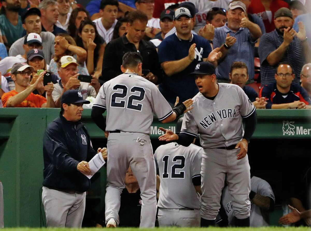 New York Yankees' Jacoby Ellsbury (22) is congratulated by teammate Alex Rodriguez, right, after he and Chase Headley (12) scored on a double by Starlin Castro during the seventh inning of a baseball game against the Boston Red Sox at Fenway Park in Boston on Wednesday, Aug. 10, 2016. (AP Photo/Winslow Townson) ORG XMIT: BXF123
