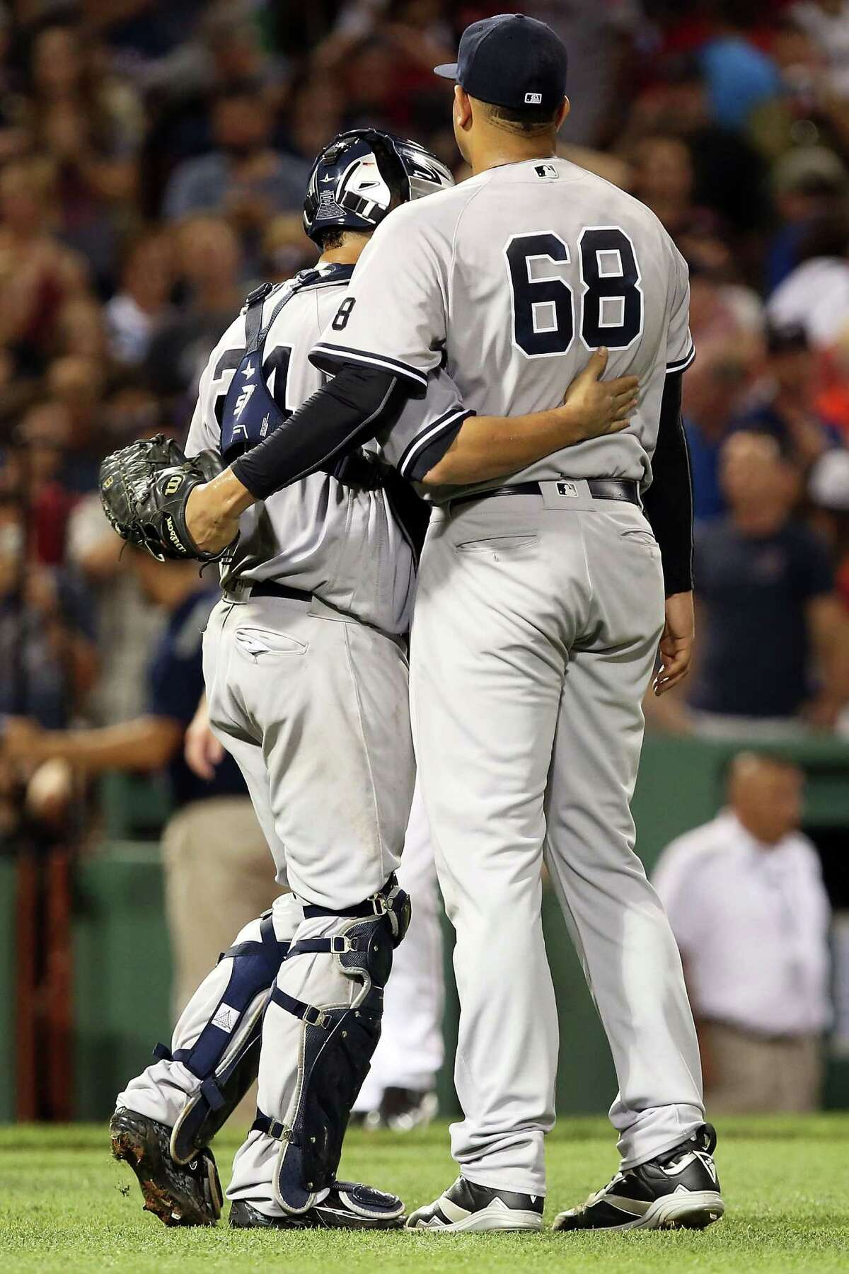BOSTON, MA - AUGUST 11: Dellin Betances #68 embraces Gary Sanchez #24 of the New York Yankees after their victory over the Boston Red Sox at Fenway Park on August 11, 2016 in Boston, Massachusetts. (Photo by Adam Glanzman/Getty Images) ORG XMIT: 607683327