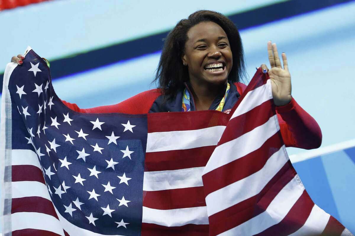 Simone Manuel gets wrapped up in the joy of the medal ceremony after winning a gold for finishing in a tie for first with Canada's Penny Oleksiak in the 100-meter freestyle.