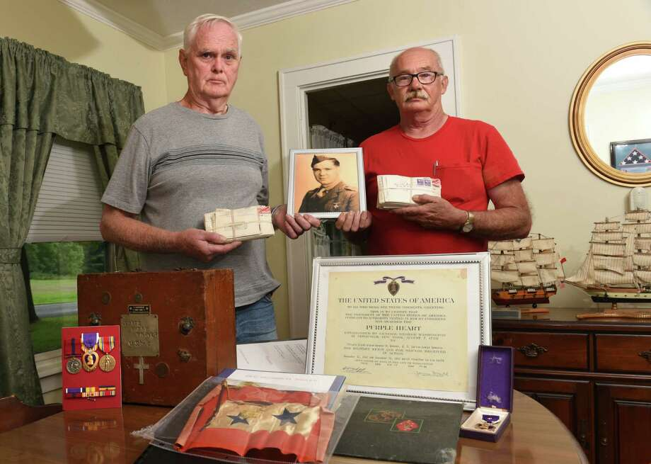 George Traver, left, holds letters from and a photo of his uncle and namesake, George Traver with his cousin David Silliman, right, at his home on Wednesday, Aug. 10, 2016 in Chatham, N.Y. George Traver, a World War II Marine, was killed in combat against the Japanese on Nov. 20, 1943 at the Battle of Tarawa. The remains were found in May, identified by the pocketknife his parents had given to him. His remains will arrive at Albany International Airport on Aug. 26 and will be taken by motorcade to his hometown of Chatham, where there will be a service and interment over the weekend. (Lori Van Buren / Times Union) Photo: Lori Van Buren / 20037605A