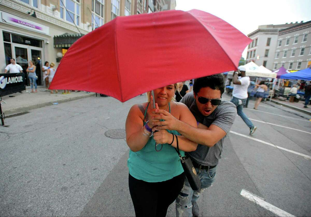 A couple runs with an umbrella as they seek shelter from a thunder storm that caused a delay in the CeeLo Green Alive@Five concert series summer finale at Columbus Park in Stamford, Conn. on Aug. 11, 2016.