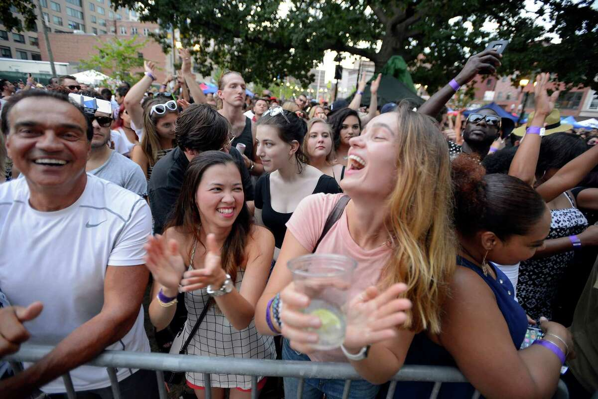 Valerie Easley of Wilton and Paula Santos enjoy the music of Wild Planes as they wait for the CeeLo Green to perform at the Alive@Five concert series summer finale at Columbus Park in Stamford, Conn. on Aug. 11, 2016.