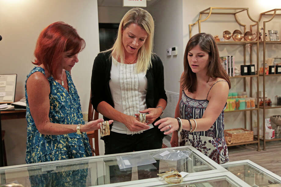 Jill Blaker (left) and daughter Danielle Blaker Nance (right) help Vera Herbert shop at B. Nance Fine Gifts, in Florence, S.C. Americans spent less at clothing shops, sporting goods stores and electronics and appliance outlets, the Commerce Department said Friday. Photo: Joe Perry /Associated Press / The Morning News