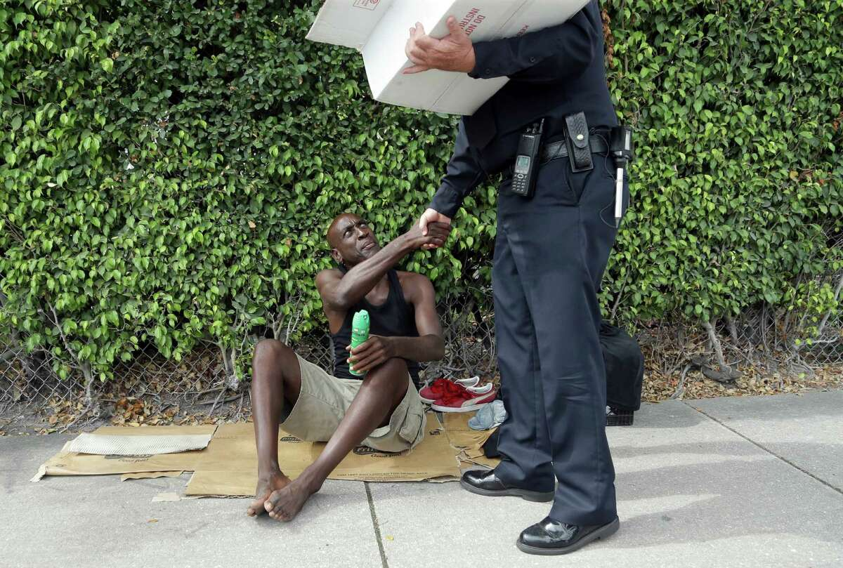 Lorenzo Ward, 45, who is homeless, shakes hands with Miami police officer James Bernat, after Bernat gave him a can of insect repellent, Tuesday, Aug. 2, 2016 in the Wynwood neighborhood of Miami. The CDC has advised pregnant women to avoid travel to this neighborhood where mosquitoes are apparently transmitting Zika directly to humans. Bernat passed out some fifty cans of spray to the homeless. (AP Photo/Lynne Sladky) ORG XMIT: FLLS102