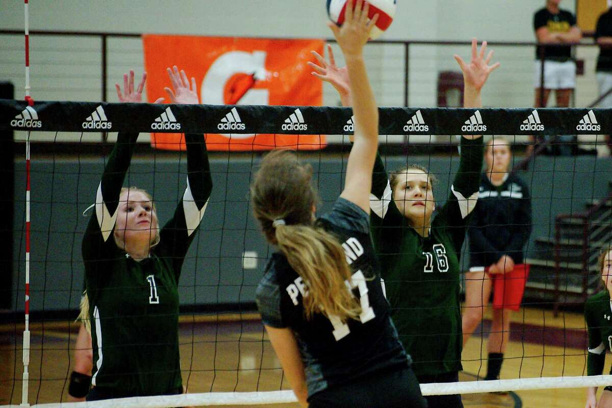 John Cooper School's Kaylee Frazier (1) and Kayley Wood (16) try to block a shot by Pearland's Sarah Wright (17) at the Adidas Texas Volleyball Invitational Thursday, Aug. 11.