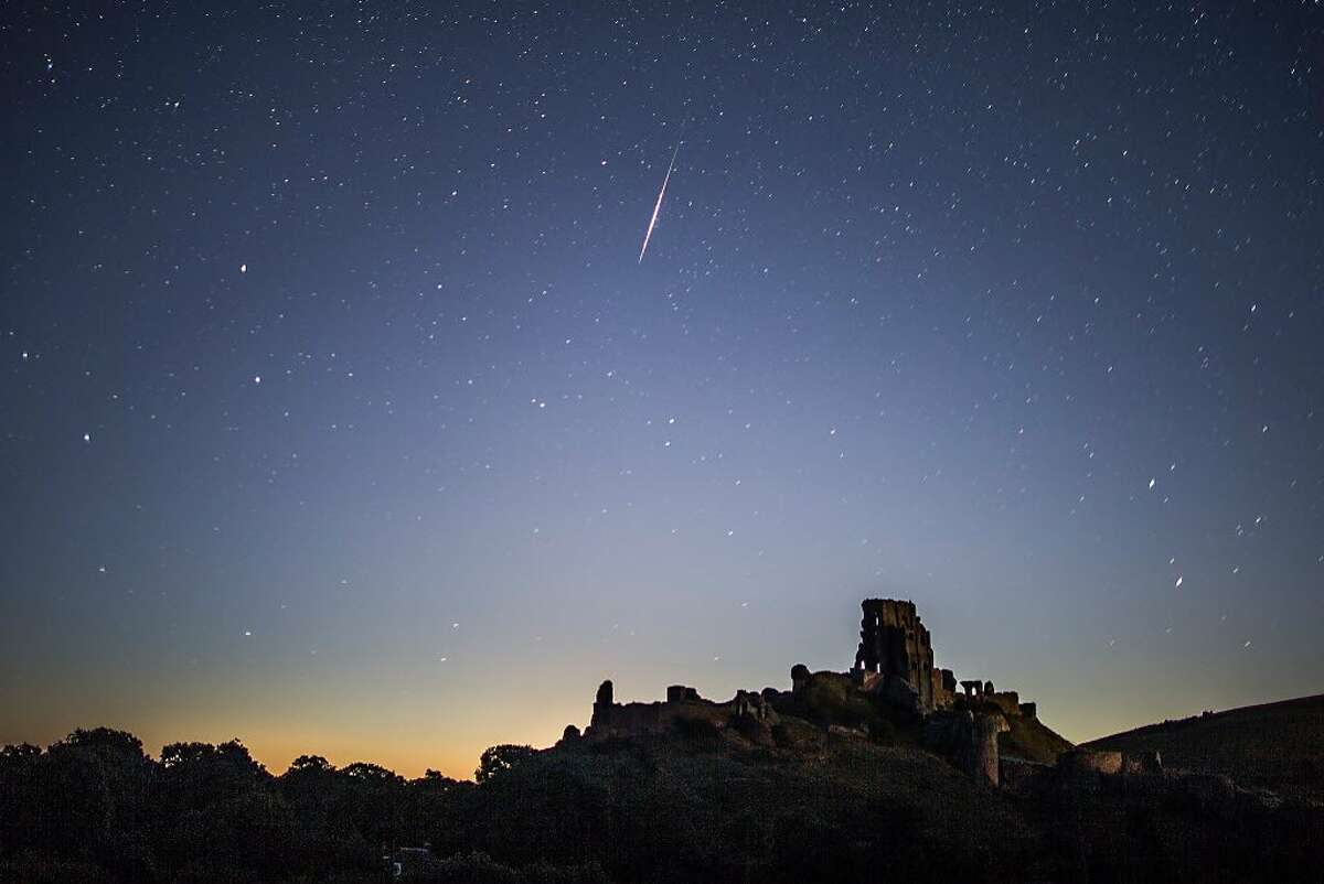 A Perseid Meteor flashes across the night sky above Corfe Castle on August 12, 2016 in Corfe Castle, United Kingdom. The Perseids meteor shower occurs every year when the Earth passes through the cloud of debris left by Comet Swift-Tuttle, and appear to radiate from the constellation Perseus in the north eastern sky.
