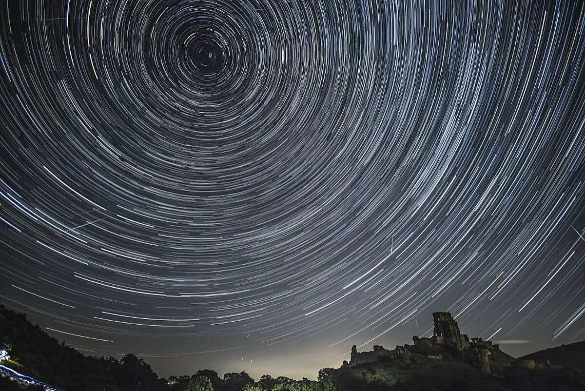 (EDITORS NOTE: THIS IS A COMPOSITE IMAGE) Satellites, planes and comets transit across the night sky under stars that appear to rotate above Corfe Castle on August 12, 2016 in Corfe Castle, United Kingdom. The Perseids meteor shower occurs every year when the Earth passes through the cloud of debris left by Comet Swift-Tuttle, and appear to radiate from the constellation Perseus in the north eastern sky.