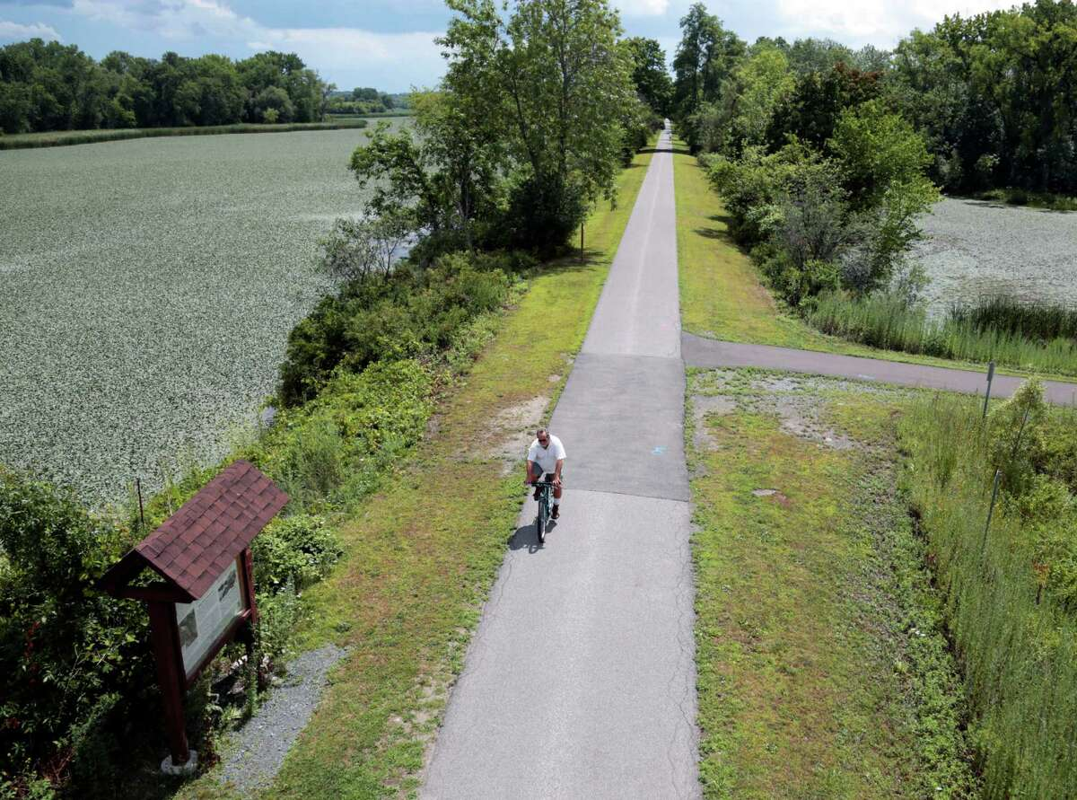 A man bikes along the Canalway Trail in Niskayuna, N.Y., in August 2015. The Erie Canal was an engineering marvel when it opened in 1825, linking the Hudson River to the Great Lakes and humming with activity that opened up the West. (AP Photo/Mike Groll)