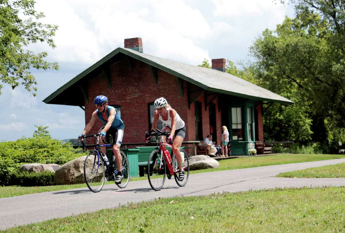 Cyclists pass the Niskayuna Train Station as they bike on the Canalway Trail in Niskayuna, N.Y., in August 2015. (AP Photo/Mike Groll)